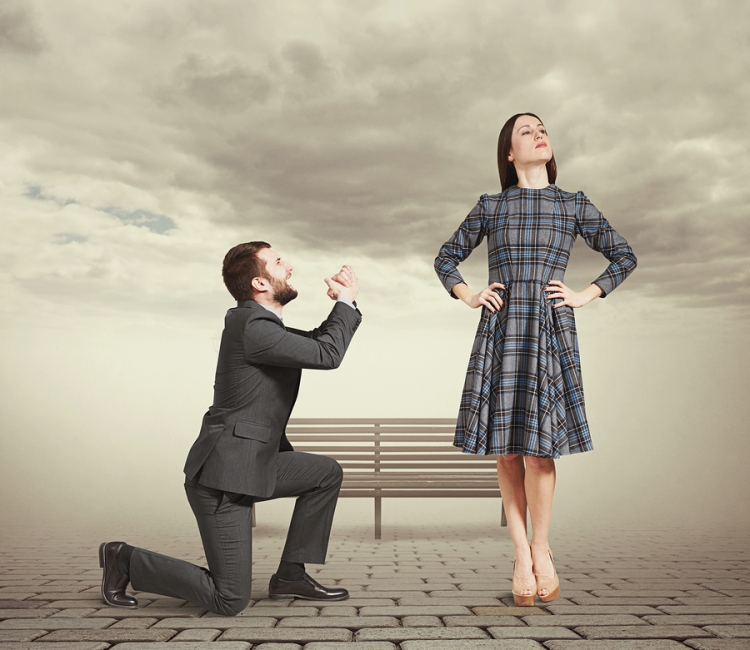 sad man kneeling on one knee, looking at young attractive woman