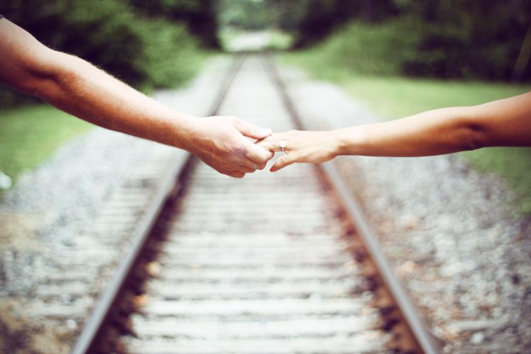 J is for Journey holding hands on train tracks sarah-cervantes-xPzMyRIUUKE-unsplash